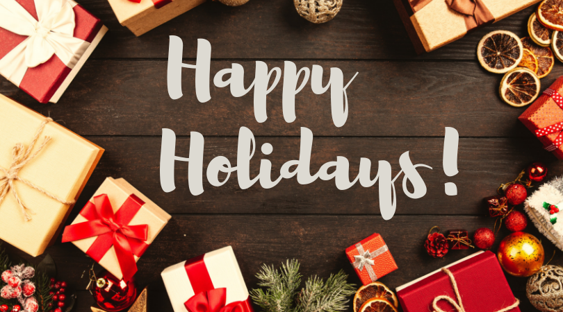 Happy Holidays in a white, fun font on a dark brown table surrounded by brightly wrapped gifts and holiday ornaments